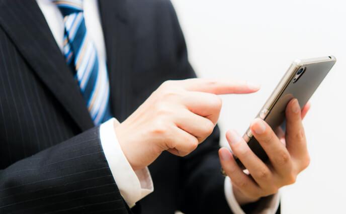 携帯を指差す男性